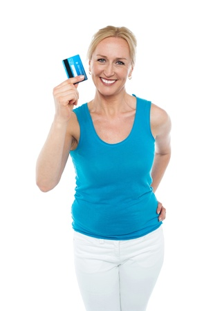 Trendy middle aged woman showing credit card to camera with hand on her waist Stock Photo - 14724650
