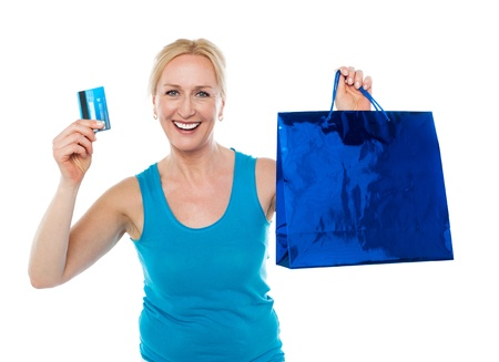 Smiling shopper woman holding bag and credit card isolated over white background Stock Photo - 14724649