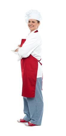 Side view of confident middle aged female chef posing with arms crossed looking at you photo