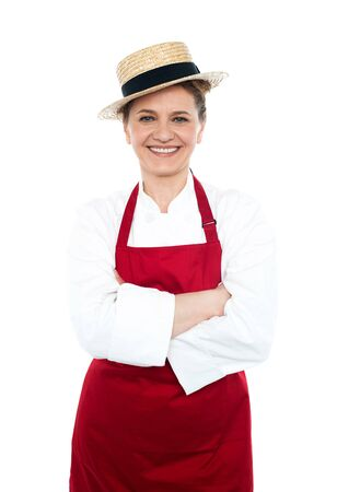 Lady cook in white red uniform wearing trendy hat and posing with crossed arms photo