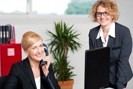 Seated woman attending call with colleague beside her, cheerful business team photo