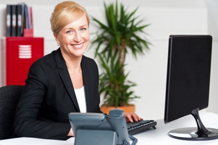 woman typing: Smiling corporate woman typing on keyboard, working in office