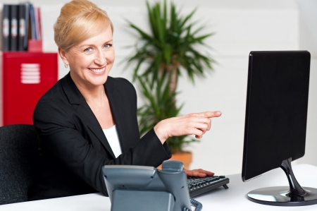 Businesswoman pointing at computer screen, seated in office photo