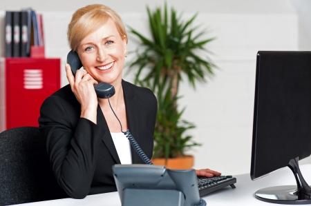 Secrétaire de parler au téléphone avec un client qui vous regarde