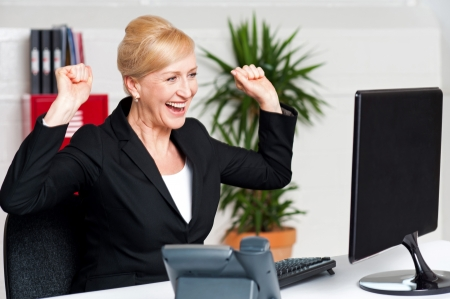 Excited corporate lady with raised arms looking at computer screen photo