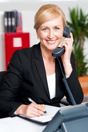 secretaries: Lady comunicaci�n corporativa en el tel�fono y confirmar el nombramiento Foto de archivo