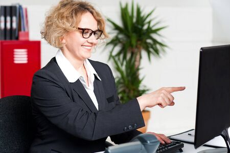 Cheerful woman pointing at something on computer screen photo