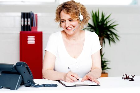 Cheerful customer support executive at work writing down customer complaints photo