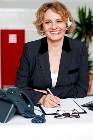 Smiling aged telemarketing woman wearing headphones sitting in office Stock Photo - 14724722