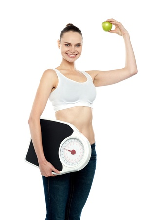 Attractive young female holding weighing machine and green apple standing against white background photo