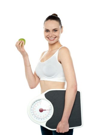 Attractive woman with apple and weight scale smiling at camera photo