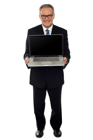 Aged businessman showing newly launched laptop, full length shot photo