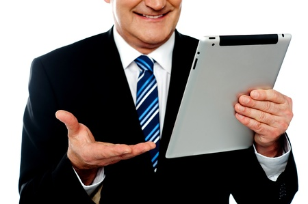 Cropped image of a businessman holding tablet pc isolated against white background photo