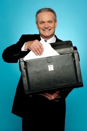 Isolated businessman keeping documents safely in a briefcase photo