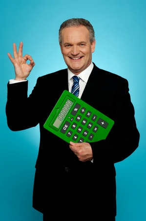 yup: Confident executive holding calculator and gesturing okay sign isolated over gradient background Stock Photo