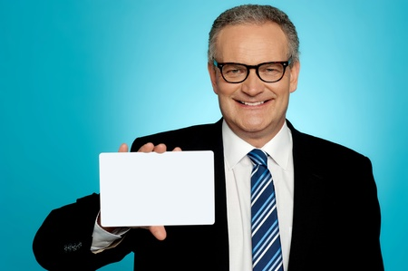 Businessman wearing glasses showing blank white placard to camera photo