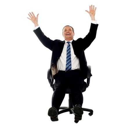 Excited businessman celebrating his success. Arms raised in air. photo