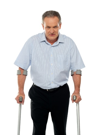 Angry aged man with crutches looking at you. All on white background photo