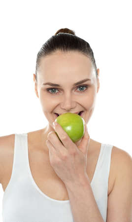 Closeup portrait of beautiful woman eating fresh green apple isolated against white background photo