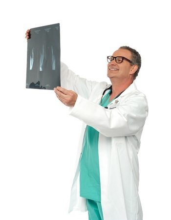 Experienced surgeon looking at x-ray report isolated over white background photo