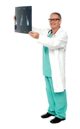 Full length shot of smiling surgeon holding x-ray report of a patient photo