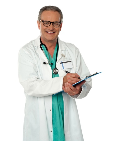 Experienced male doctor looking at you  and making report photo