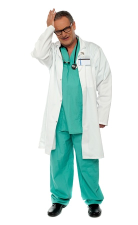 Full length shot of unhappy doctor in uniform isolated over white background photo