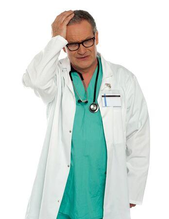 Senior physician having headache. Holding his head