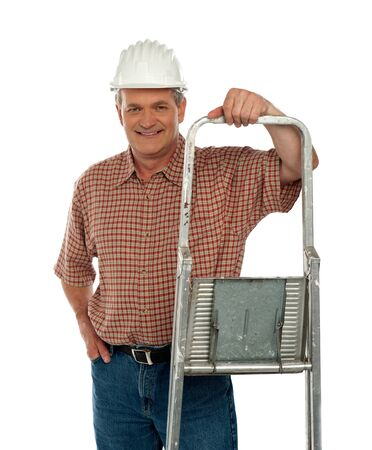 Smiling aged worker posing with ladder isolated against white background photo