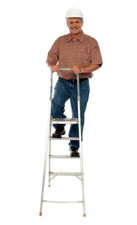Worker wearing hard hat climbing ladder. All on white background photo