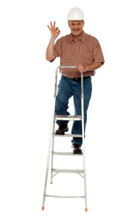 Contraction worker with excellent gesture climbing on ladder, full length portrait photo