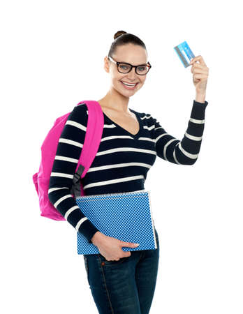 Teenager showing credit card to camera and holding spiral book isolated over white background photo