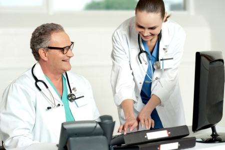Smiling medical team working on computer in a hospital photo