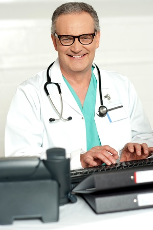 eye wear: Smiling physician in eye wear typing on keyboard and looking at you Stock Photo