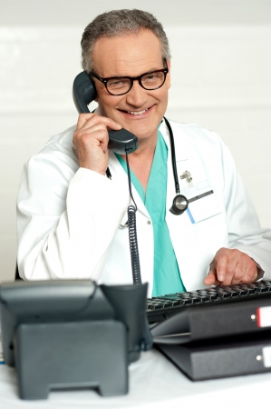 Matured physician communicating on phone sitting on chair in his lab photo