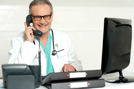 man doctor: Aged doctor attending call in front of lcd screen smiling at camera
