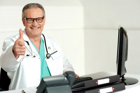 Smiling doctor gesturing thumbs up to camera while working in his clinic photo