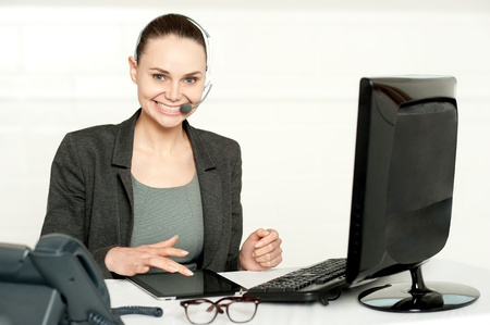 Customer care executive using tablet pc wearing headsets and looking at camera photo