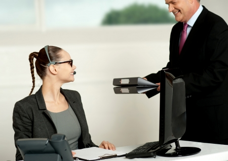 Business team of two working in office. Woman sitting in chair while man presenting files to her photo