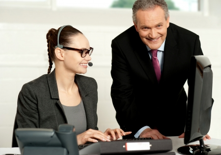 Successful business team working together. Woman typing on keyboard and aged man looking at you photo