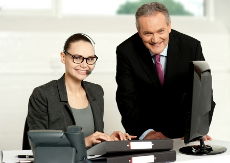 Cheerful corporate people at work in office. Woman typing on keyboard photo