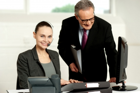 Team of two business executives working in office in front of computer photo