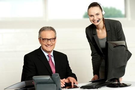 Successful team of senior man and young woman looking at camera photo