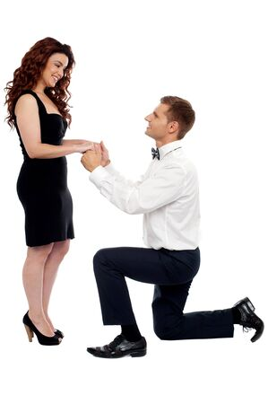 Handsome guy on knees proposing girl. Will you marry me? photo