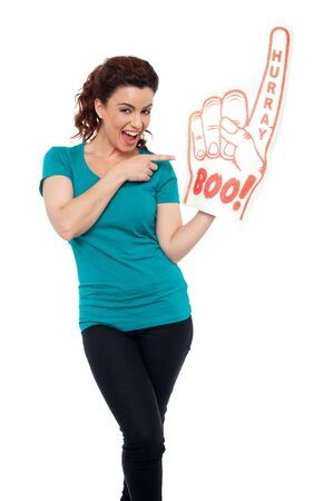 Smiling young woman pointing at large foam hand isolated against white background photo