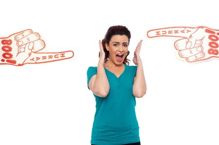 hurray: Woman shouting loud, stuck in between two large hurray boo foam hands pointing at her Stock Photo