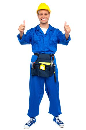 Successful young worker gesturing double thumbs up with tool box wrapped around his waist Stock Photo - 15030217