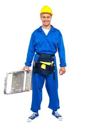 Full length portrait of happy young construction worker ready for work holding a stepladder photo
