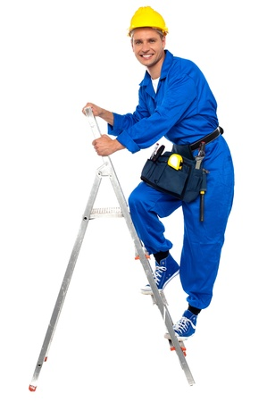 Repairman climbing up a stepladder  with tool box wrapped around his waist photo