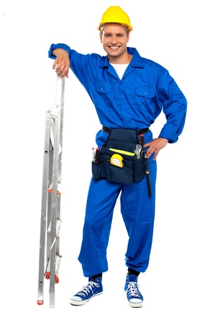 Full length portrait of smiling Industrial contractor resting hand on stepladder photo